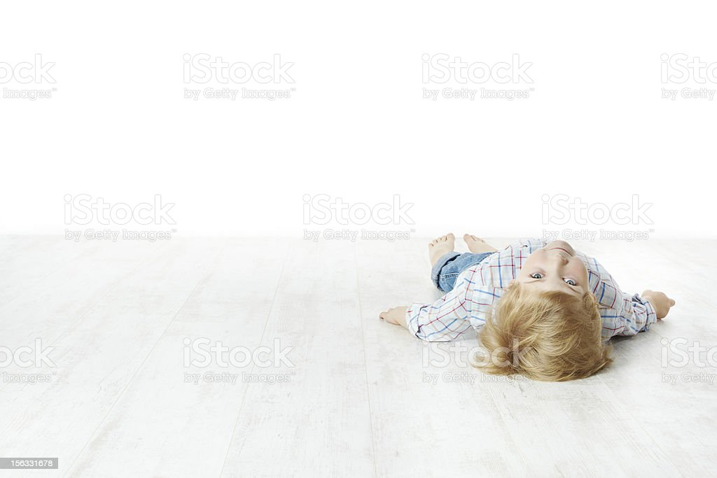 Little boy lying down on floor royalty-free stock photo