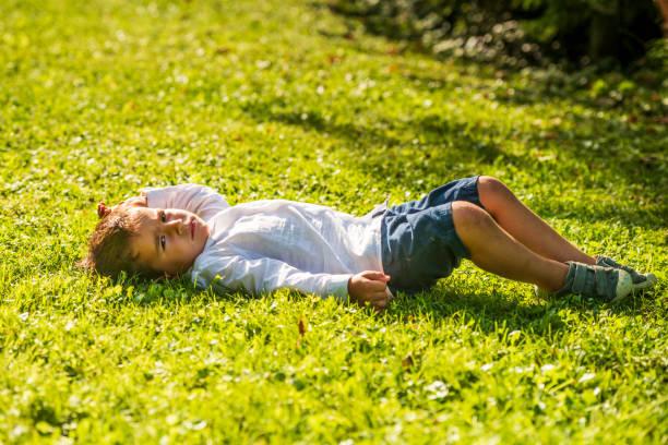kleiner junge liegt im gras - kemter stock-fotos und bilder