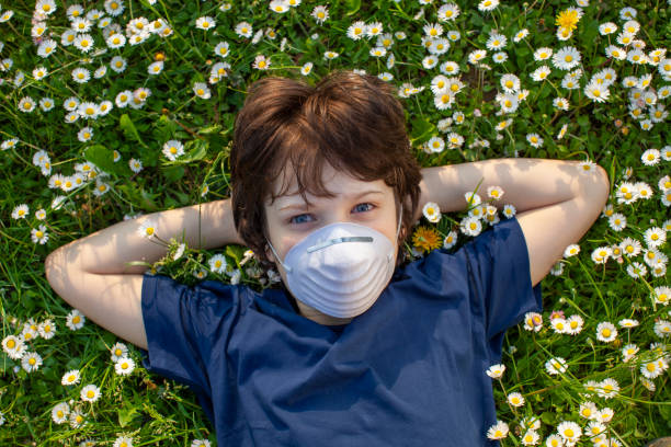 Little boy lying on a flowery meadow with protective mask stock photo