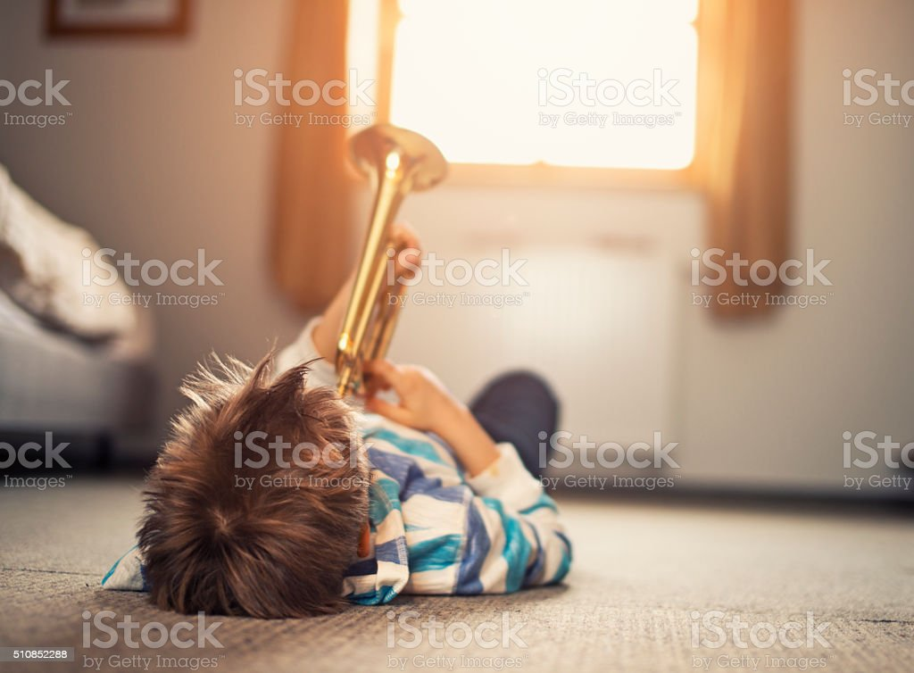 Little boy lying on back and playing trumpet stock photo