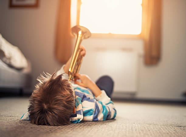 kleine junge liegend zurück und trompete zu spielen - lautbildungsspiele stock-fotos und bilder