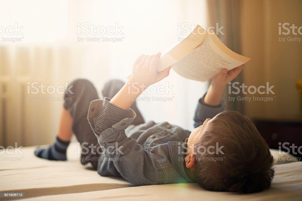 Kleiner Junge lesen liegend auf der Rückseite und ein Buch – Foto