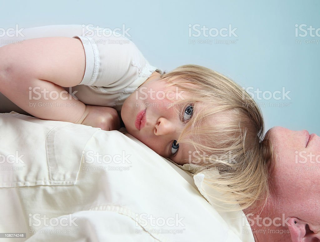 Little Boy Lying on Sleeping Father's Chest royalty-free stock photo