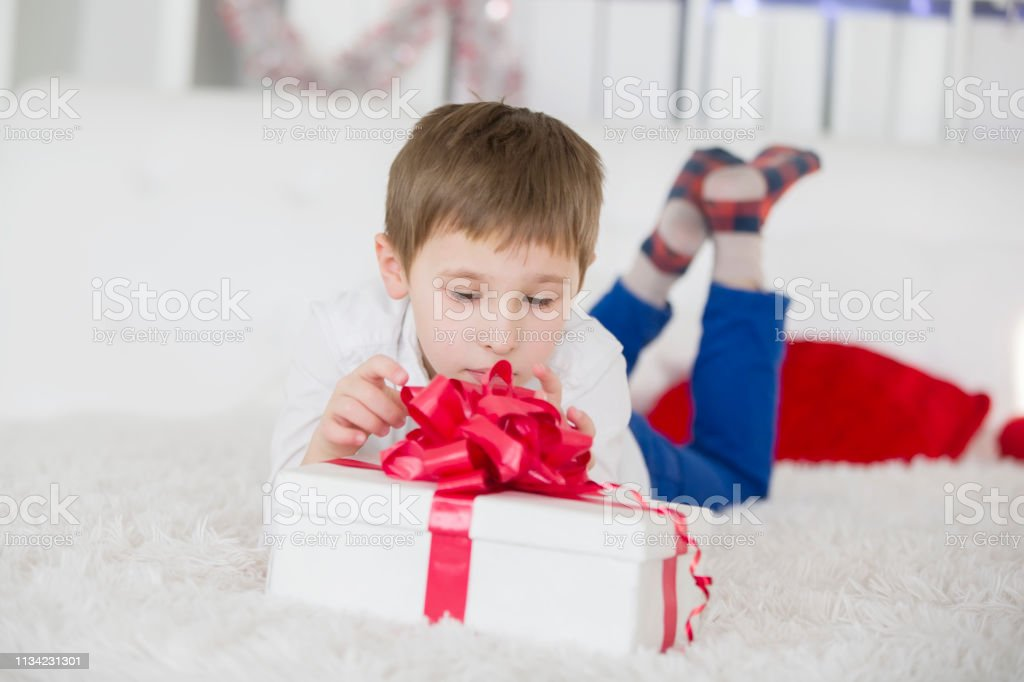 A little boy lying on the bed opens a gift. Get a box with a gift