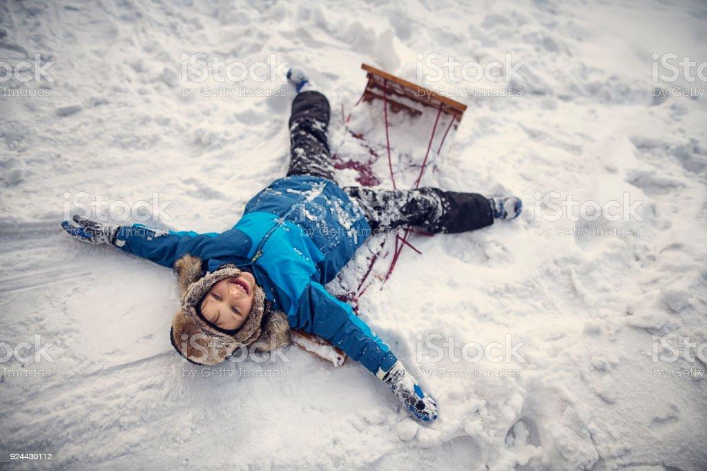 Petit garçon couché sur la piste de luge dans la neige - Photo