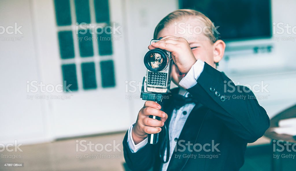 Little boy makes a movie with retro video camera stock photo