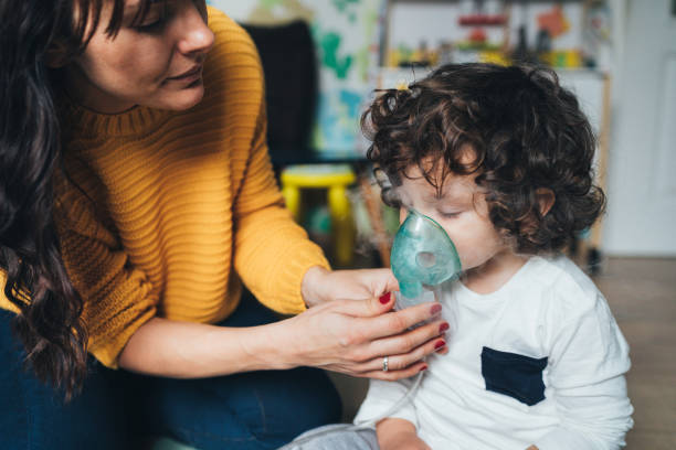 Little boy makes inhalation at home stock photo