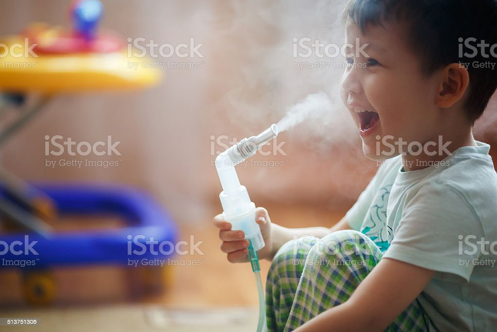 Little boy makes inhalation at home, taking medication to bronchial Little boy makes inhalation at home, taking medication to the bronchial tubes. Exhales steam through the tube. Child Stock Photo