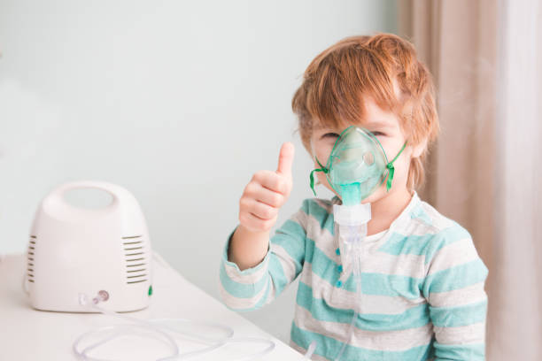 Little boy making inhalation with nebulizer at home. Little boy making inhalation with nebulizer at home. smoke inhalation stock pictures, royalty-free photos & images