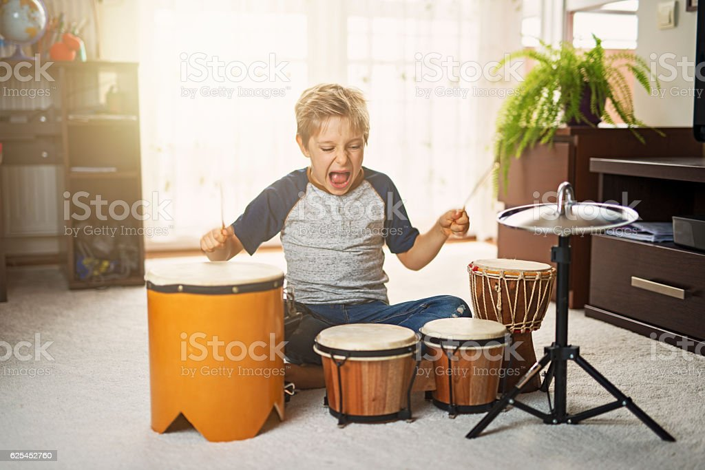 Little boy making noise on makeshift drums stock photo