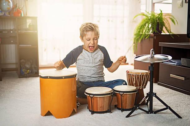 little boy making noise on makeshift drums - lautbildungsspiele stock-fotos und bilder
