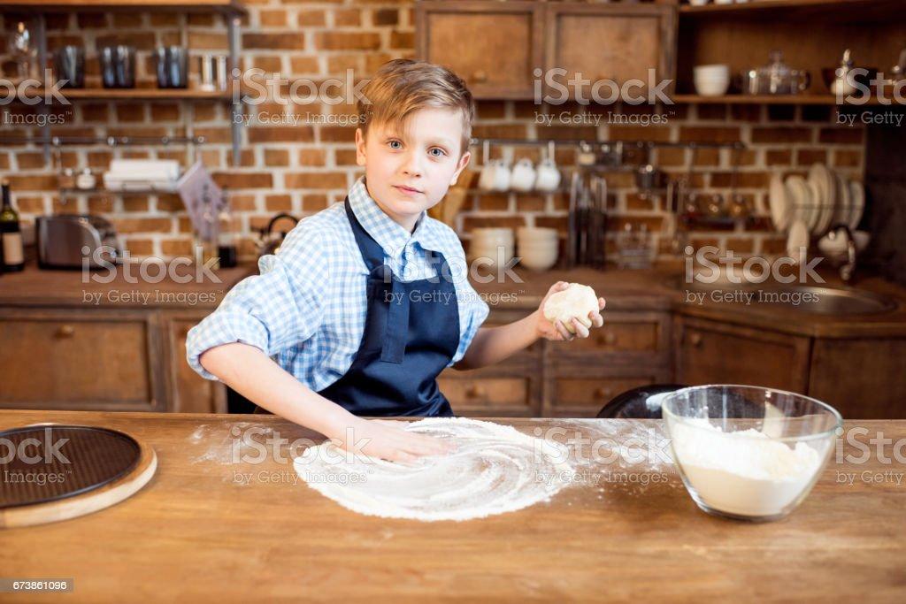 küçük çocuk mutfakta ahşap masa üstü pizza hamur yapma royalty-free stock photo