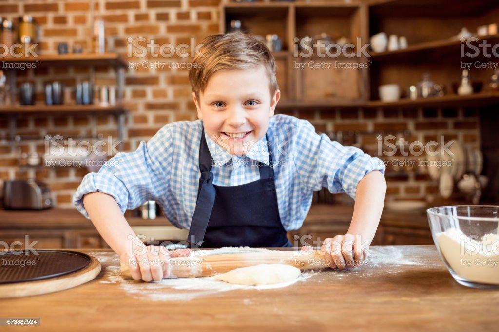 petit garçon faire pâte à pizza sur une table en bois dans la cuisine photo libre de droits