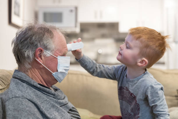 Little Boy measuring temperature of his sick Grandfather with infrared thermometer stock photo