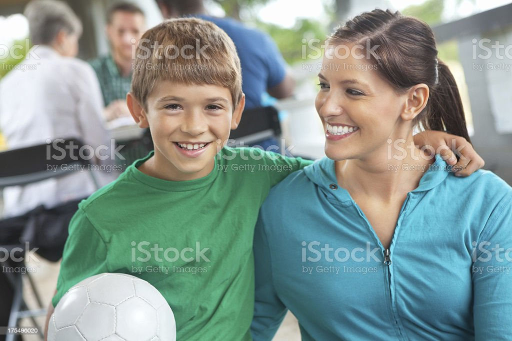 Little boy & mom at soccer sign-ups in park stock photo