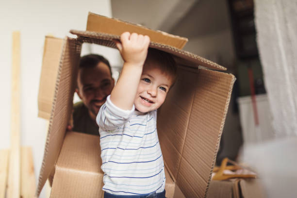 liten pojke flyttar till sitt nya hem - flyttlådor bildbanksfoton och bilder
