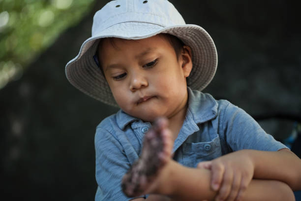 A little boy observes and is concerned about his dirty feet after playing outdoors in the mud. stock photo