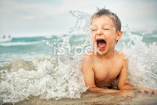 Portrait of a happy little boy splashed by wave on the beach.