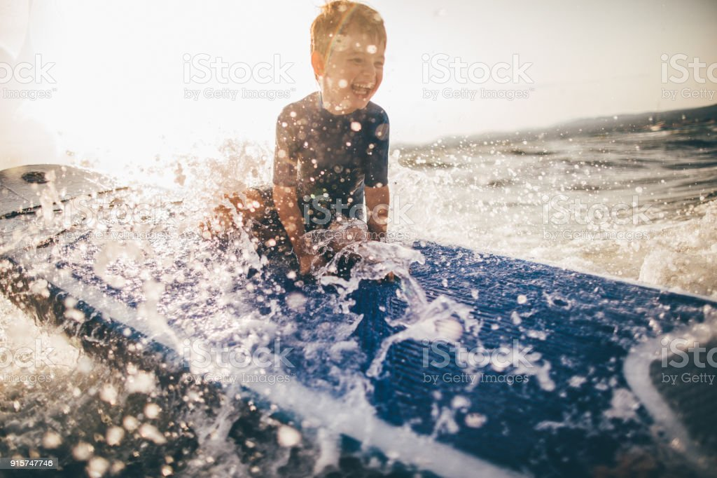 Little boy on a surfboard stock photo