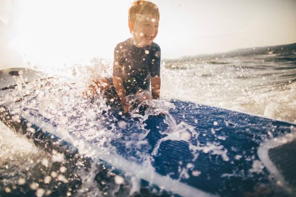 kleiner junge auf einem surfbrett - wassersport stock-fotos und bilder