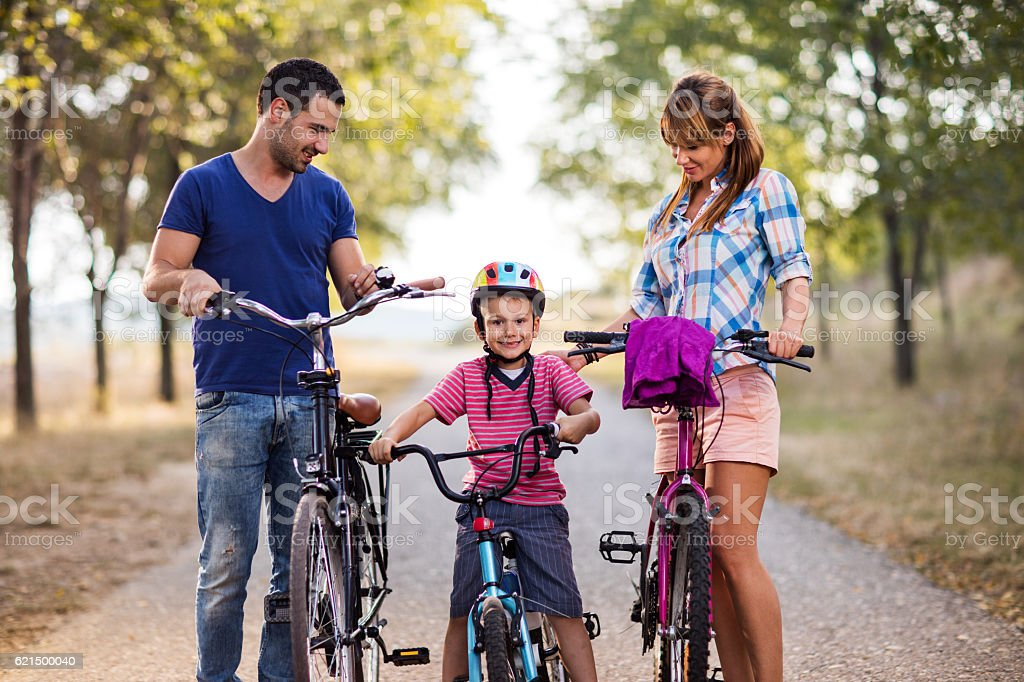 Little boy on bicycle enjoying in nature with parents. photo libre de droits