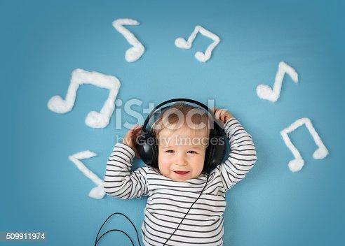 istock little boy on blue blanket background with headphones 509911974