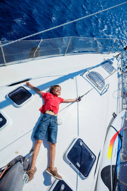 Little boy on board of sailing yacht on summer cruise. Travel adventure, yachting with child on family vacation stock photo