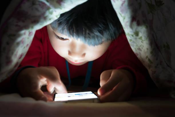 Kleiner Junge am Handy unter Bettdecke – Foto