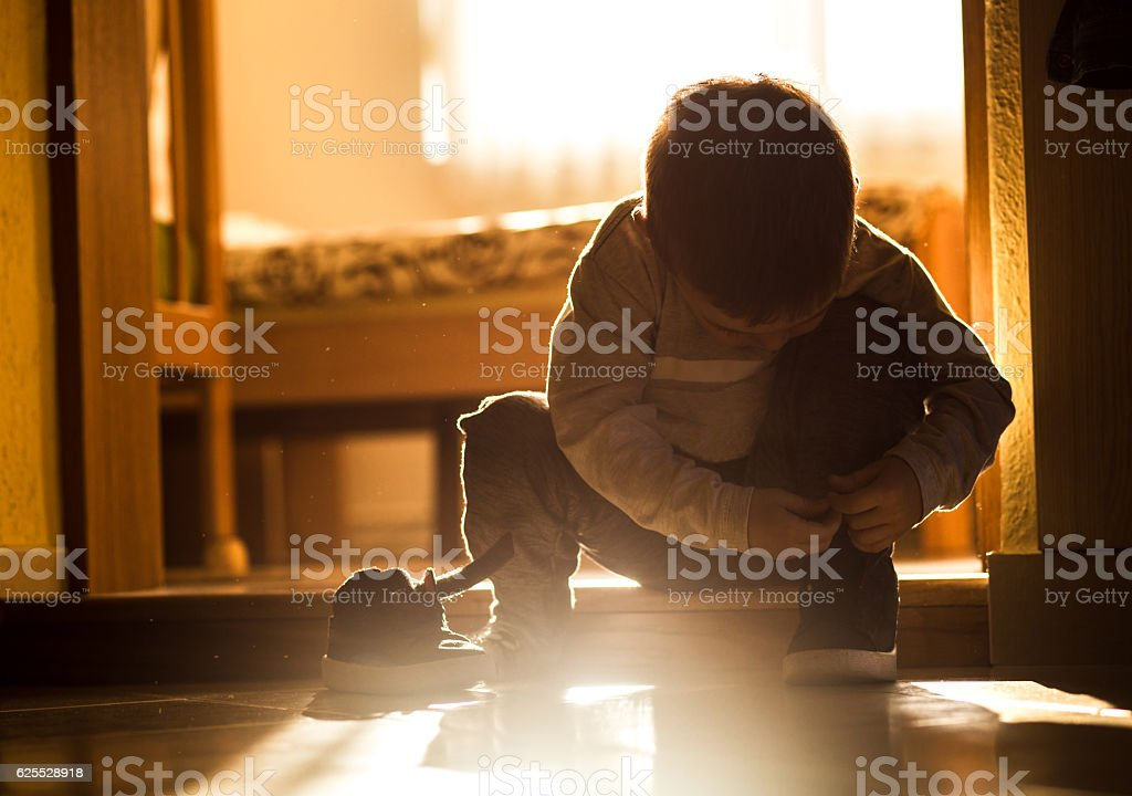 Little boy on doorstep trying to put his shoes on stock photo