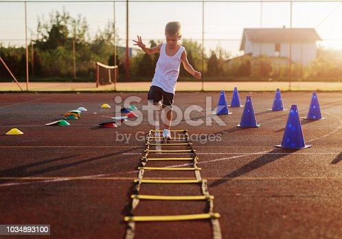 istock Little boy on early morning summer training jumping over trammels in training field. 1034893100