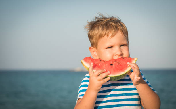 Little boy on holiday eating watermelon stock photo