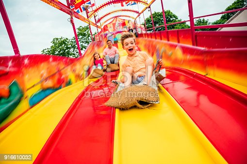 Little boy having fun sliding down a yellow and red slide while sitting in a burlap sack