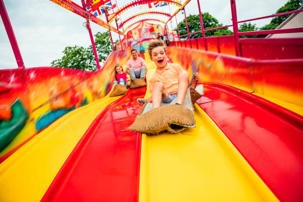 Little boy on Slide at a Funfair Little boy having fun sliding down a yellow and red slide while sitting in a burlap sack leisure equipment stock pictures, royalty-free photos & images