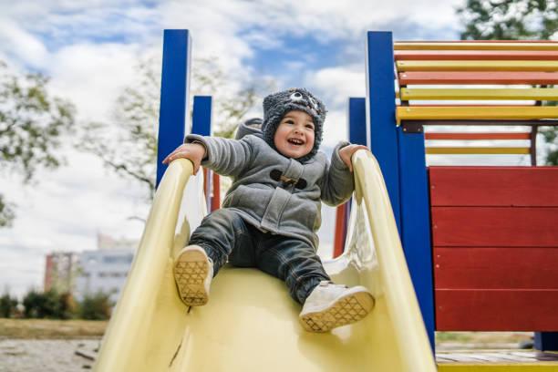 jongetje op de eerste dia in het park - speeltuin stockfoto's en -beelden