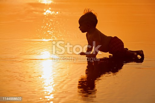 istock Little boy on sunset sea beach 1144558522