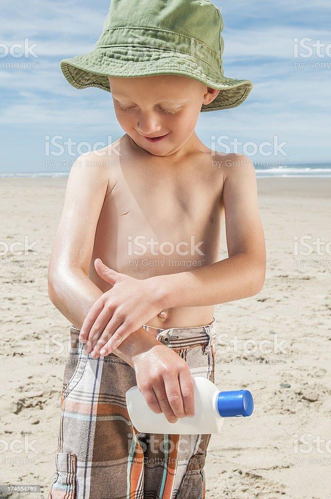 Little boy on the beach applying sunscreen. royalty-free stock photo