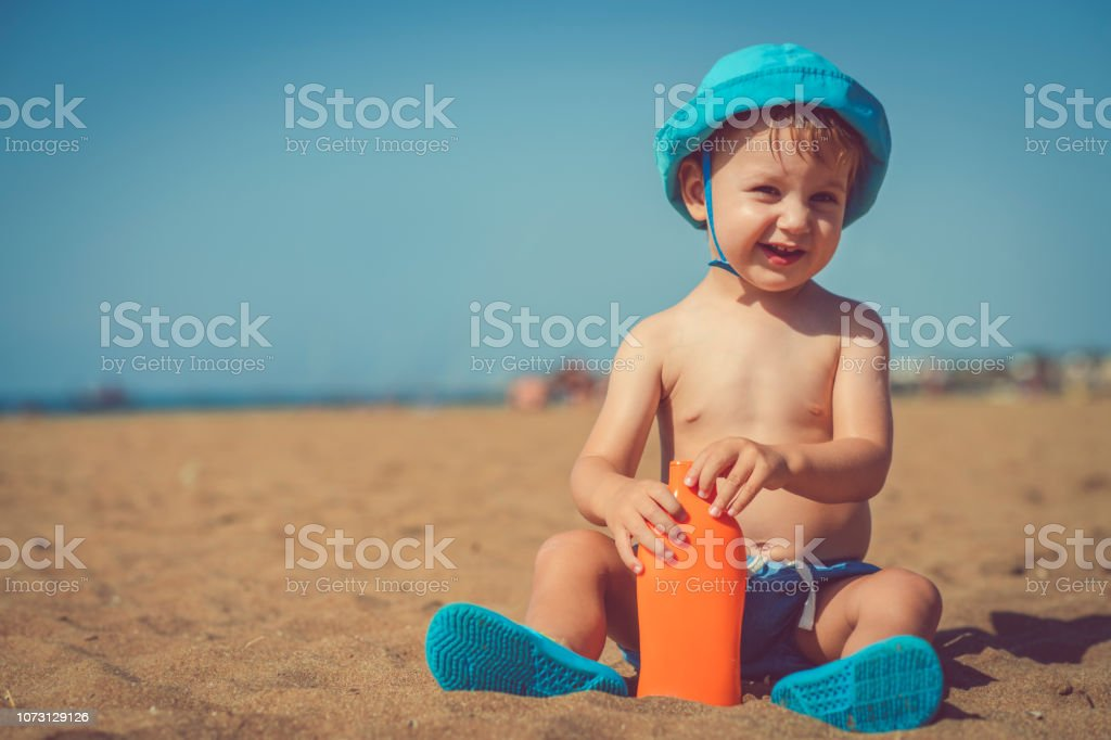 Little boy on the beach with sun protection lotion stock photo