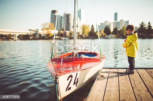istock Little boy on the river dock 475777070