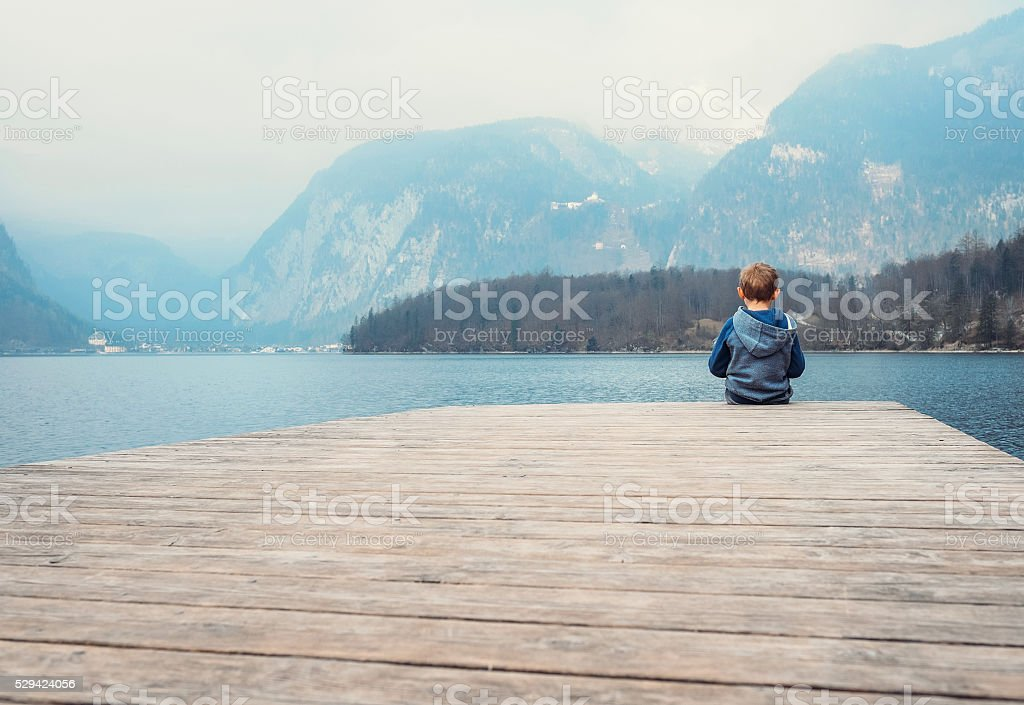 Little boy on the wooden pier near blue mountain lake stock photo