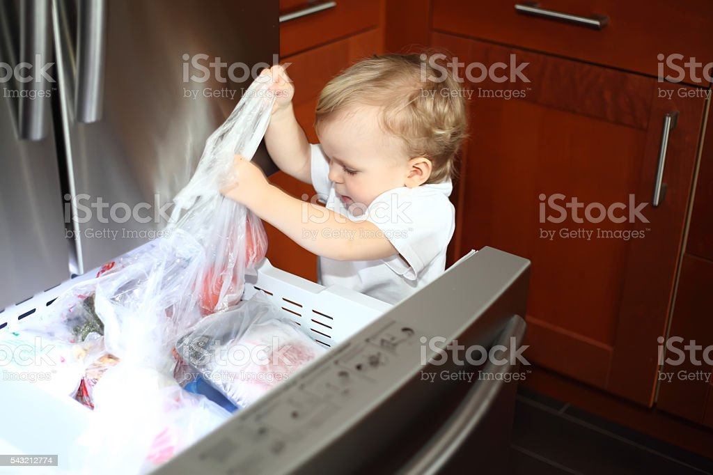 Little boy opened the freezer door and taking things out stock photo