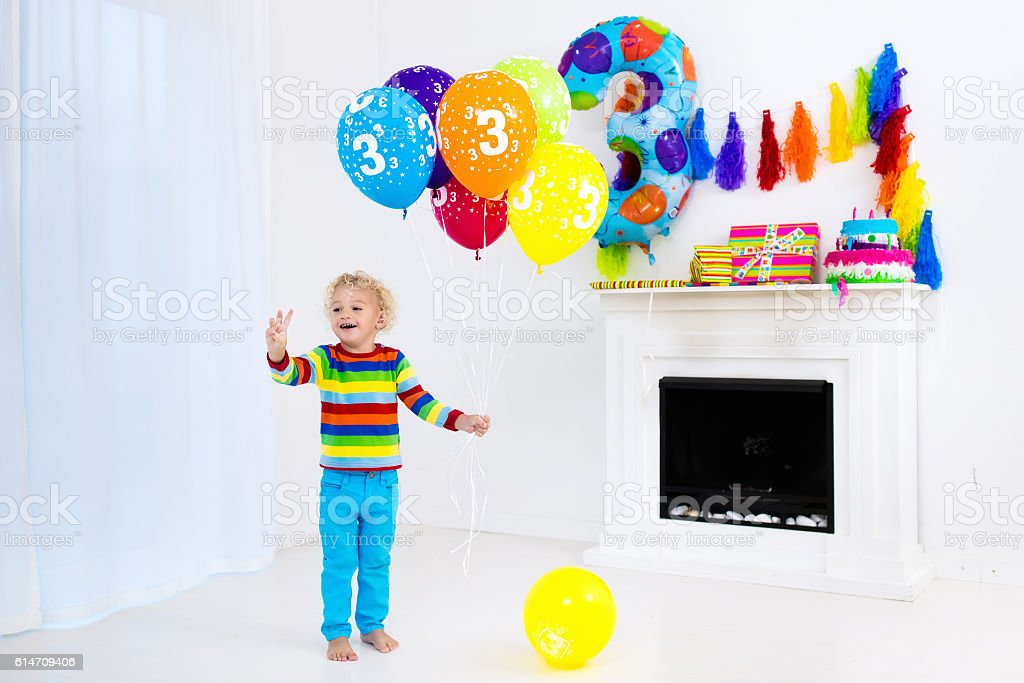 Little boy opening birthday presents stock photo