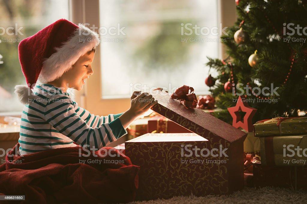 Little boy opening Christmas present stock photo