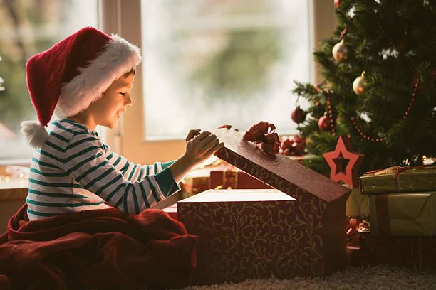 kleiner junge öffnen weihnachtsgeschenk - deckenleuchte kinderzimmer stock-fotos und bilder