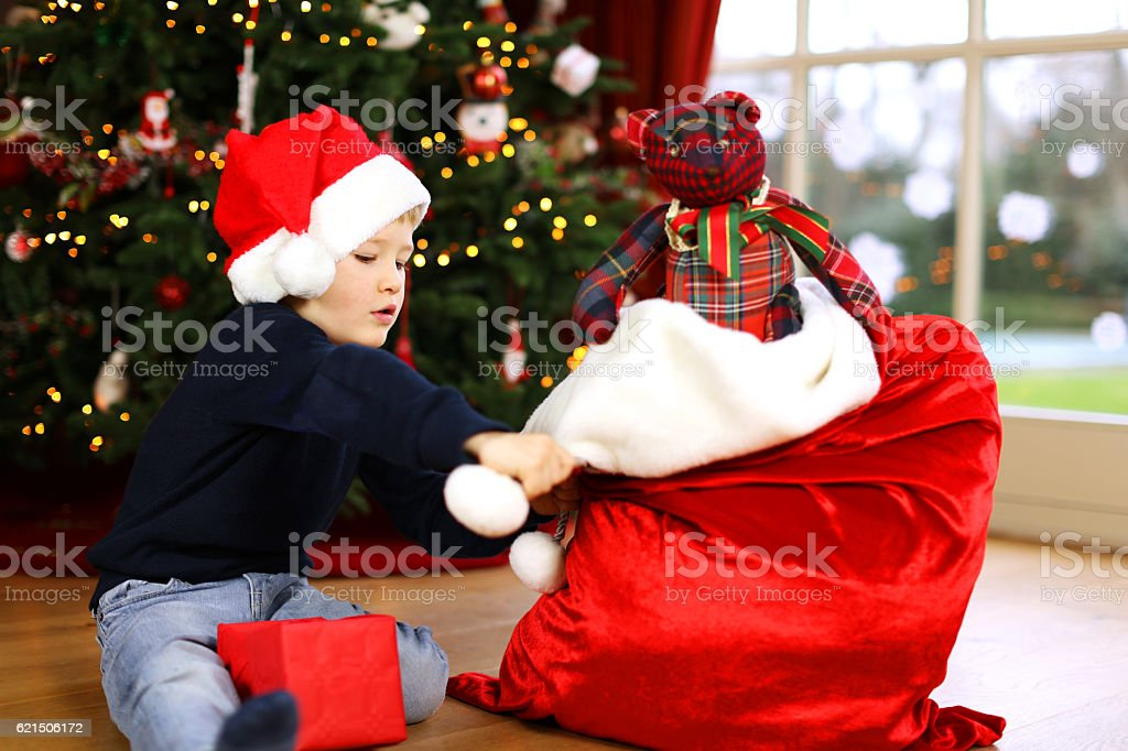 Little Boy Opening Santa's Bag Full of Christmas Presents foto stock royalty-free