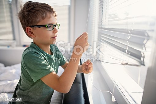 Little boy opening the blinds in the morning on sunny day.
