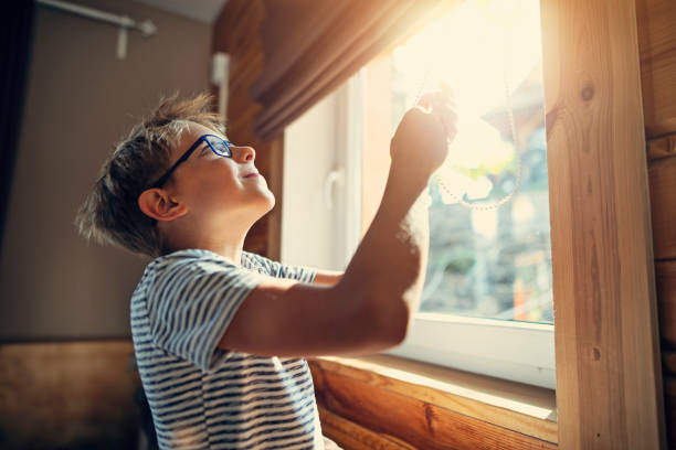Little boy opening the roller blinds in the morning stock photo