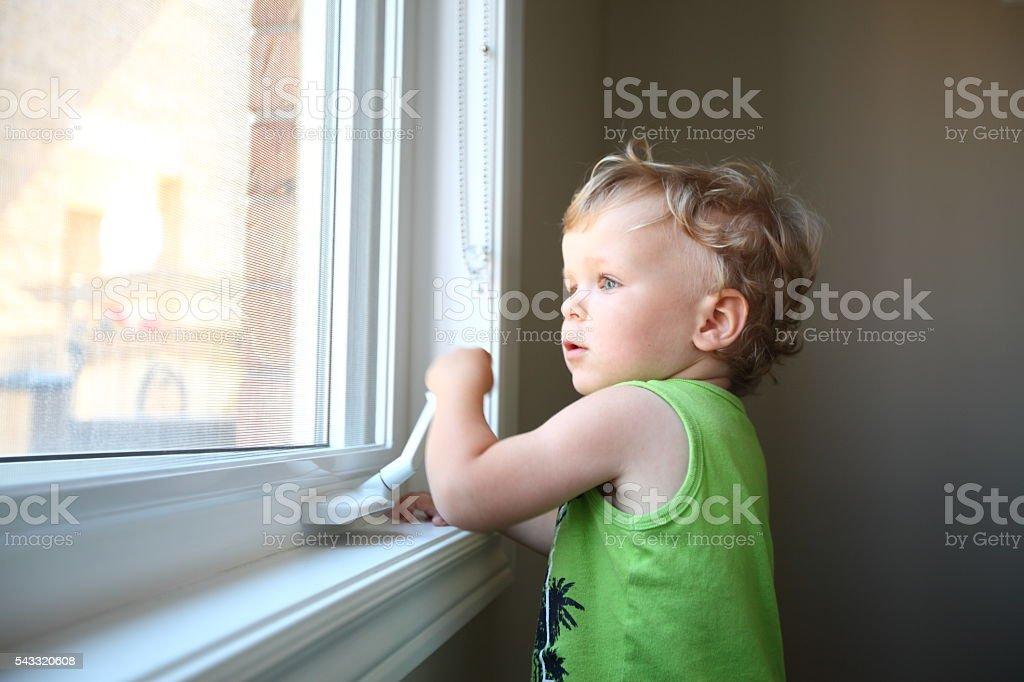 Little boy opening the window stock photo