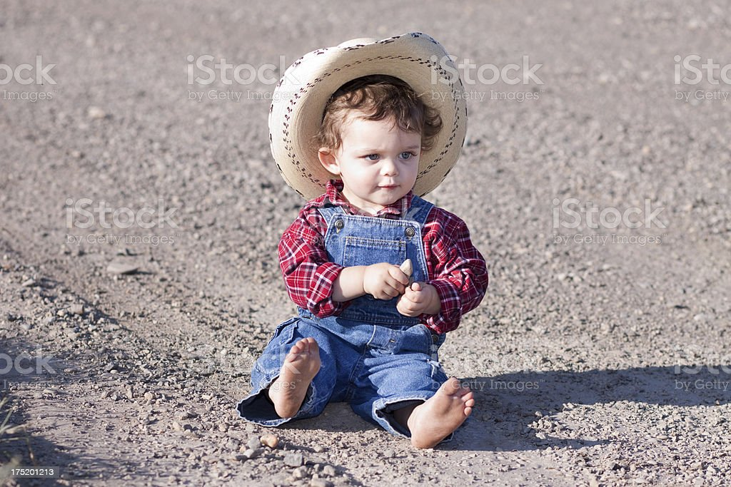 Little Boy Outdoors in Blue Denim Overalls and Cowboy Hat royalty-free stock photo