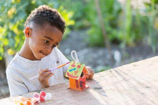 Little boy (5 years) painting bird house.