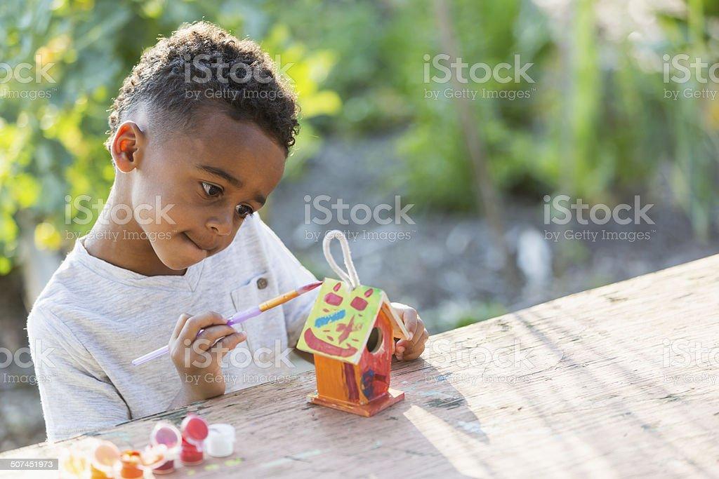 Little boy painting bird house stock photo